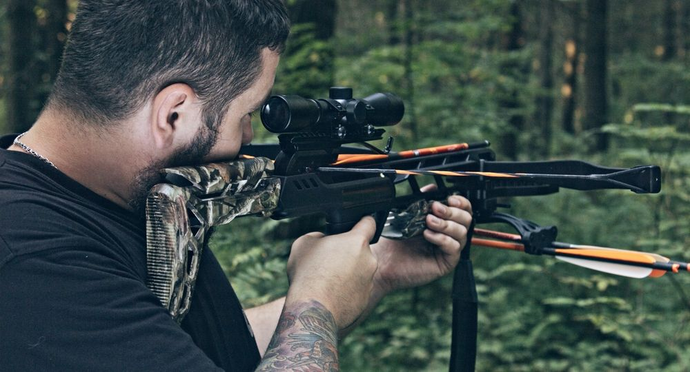 A man with a crossbow in the woods. Shooter.